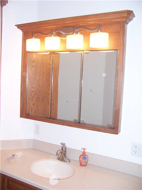 Red oak medicine cabinet with mirror doors - Corian solid surface countertop with integral sink
