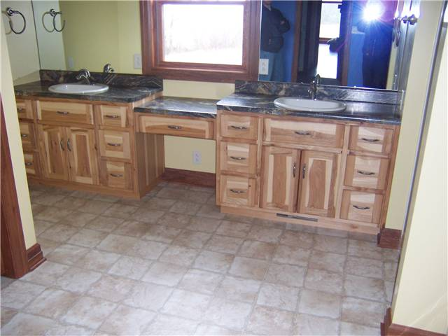 Rustic hickory cabinets - Flat panel doors and drawer fronts - Standard overlay style - Laminate countertops with drop-in sinks