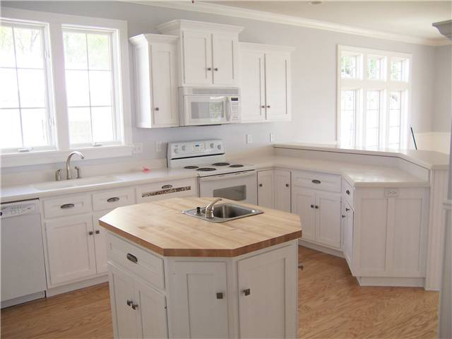 Painted cabinets - Flat panel doors, drawer fronts, and side panels - Solid surface countertops on the perimeter and a butcher block countertop on the island