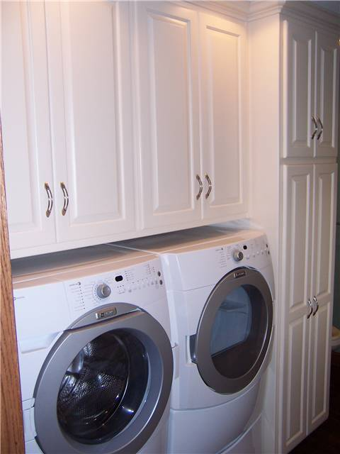 Painted cabinets enclose the washer and dryer