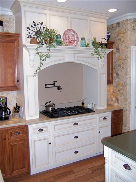 Cooking area featuring a painted wood cooking enclosure with an exhaust hood
