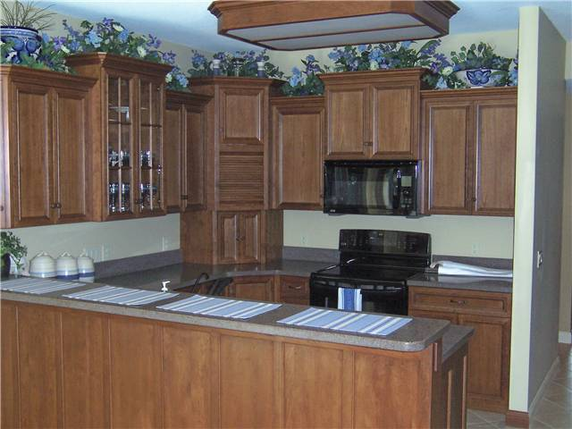Cherry cabinets - Flat panel miter corner doors - Full overlay style - Solid surface countertops