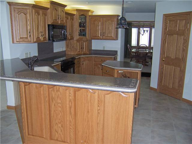 Red oak cabinets - Raised panel doors and side panels - Standard overlay style - Solid surface countertops