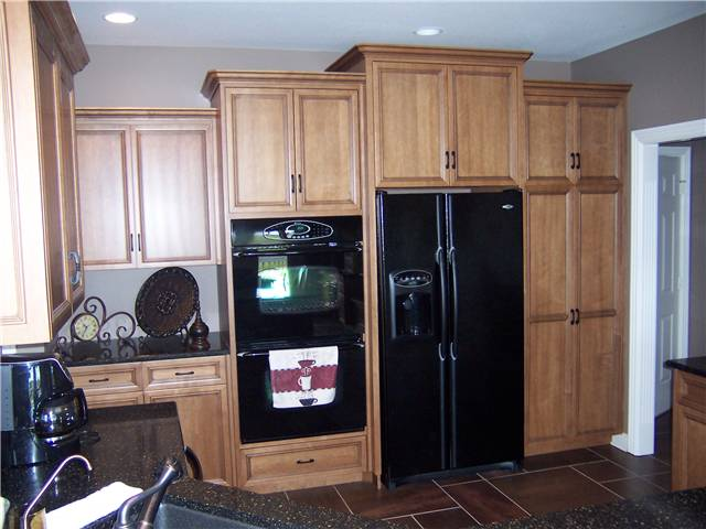 Maple cabinets stained with a glazed finish - Flat panel miter corner doors and drawer fronts - Full overlay style - Quartz countertops