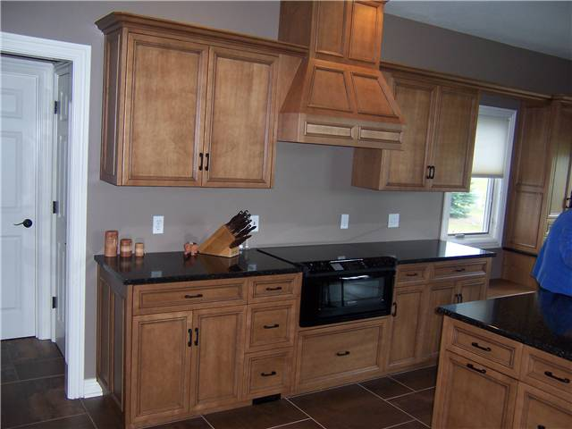 Maple cabinets stained with a glaze finish - Flat panel miter corner doors, drawer fronts, and side panels - Full overlay style - Quartz countertops