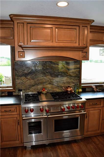 Stained and glazed maple cabinets - commercial range - commercial wood range hood - granite countertop and backsplash