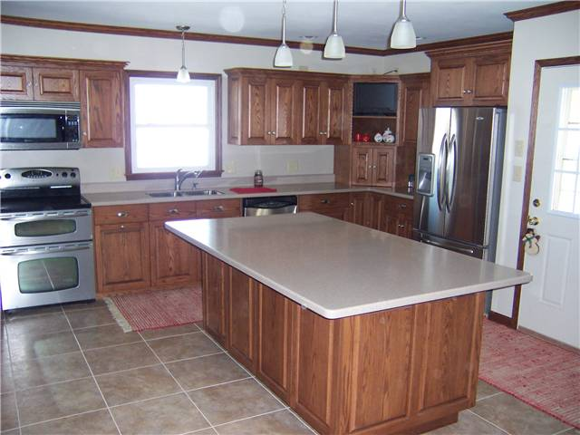Red oak cabinets - Raised panel doors and drawer fronts - Full overlay style - Corian solid surface countertops