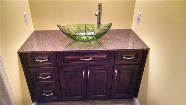 Stained hickory cabinet - cultured granite countertop - glass vessel sink