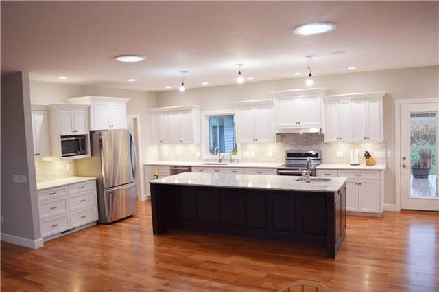 Painted perimeter cabinets - Stained rustic hickory island - Quartz countertops