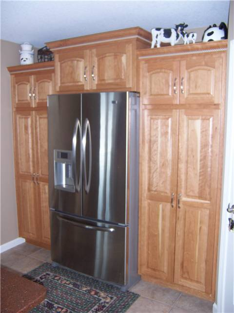 Cherry pantry cabinets with natural finish - Raised panel doors - Standard overlay style
