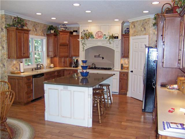 Hickory cabinets - Painted island and cooking area - Flat panel miter corner doors, drawer fronts and side panels - Standard overlay style - Corian solid surface countertops