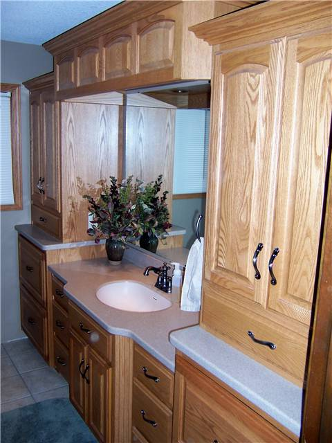Red oak cabinets - Raised panel doors - Standard overlay style - Corian solid surface countertops with an integral sink