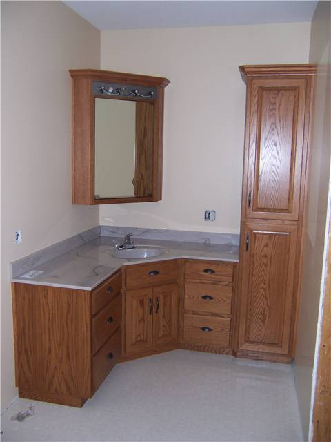 Red oak cabinets - Raised panel doors - Standard overlay style - Cutured marble countertop with an integral sink