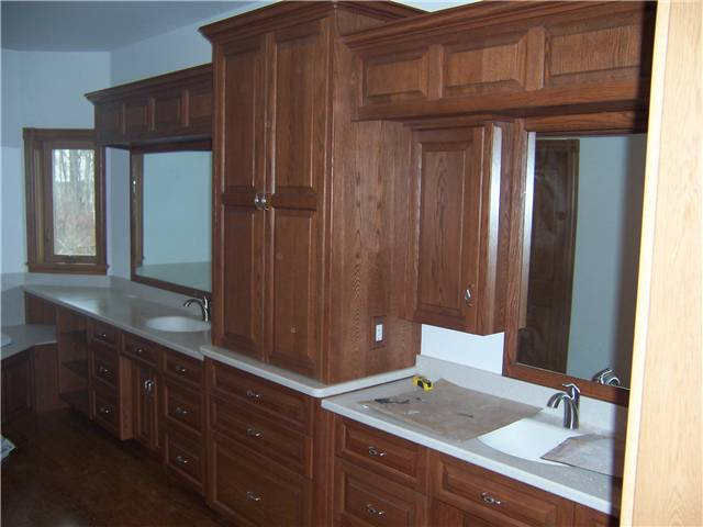 Red oak cabinets - Raised panel doors and drawer fronts - Full overlay style - Corian solid surface countertops with integral sinks
