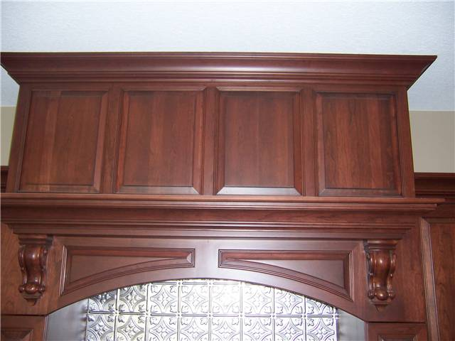 Custom wood range vent hood with raised panels and corbels