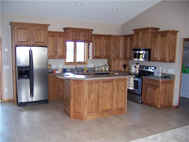 Red oak cabinets - Island with raised bar - Raised panel doors and side panels - Standard overlay style - Laminate countertops