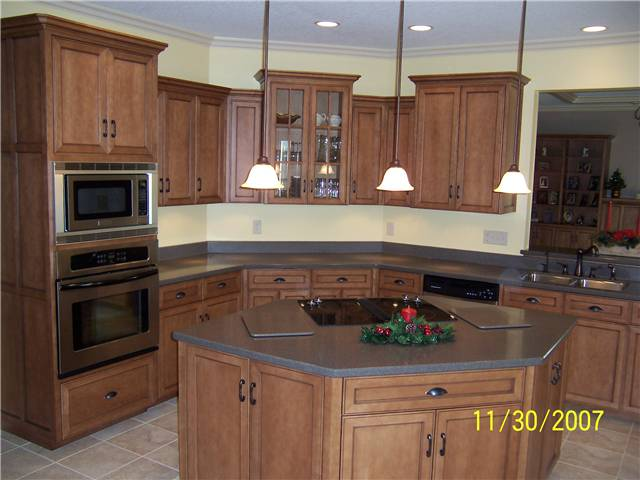 Maple cabinets stained with a glaze finish - Flat panel miter corner doors, drawer fronts, and side panels - Full overlay style - Corian solid surface countertops