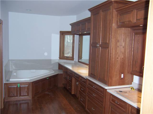 Red oak cabinets - Raised panel doors, drawer fronts, and tub access panels - Full overlay style - Corian solid surface countertops with integral sinks - Corian tub deck and backsplash