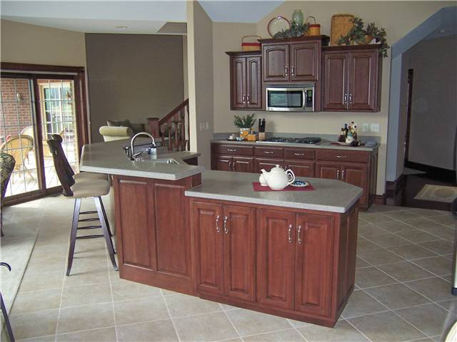 Hickory cabinets - Island with raised bar - Raised panel doors - Standard overlay style - Corian solid surface countertops