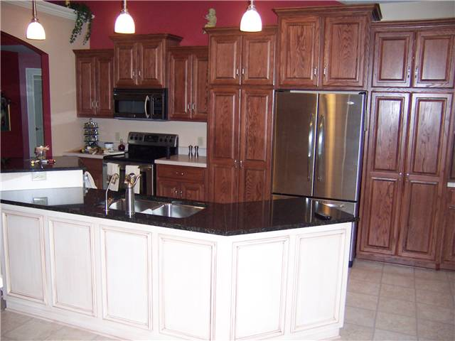 Red oak cabinets with a painted and glazed island - Raised panel doors - Standard overlay style - Granite countertop on the island with a stainless steel undermount sink