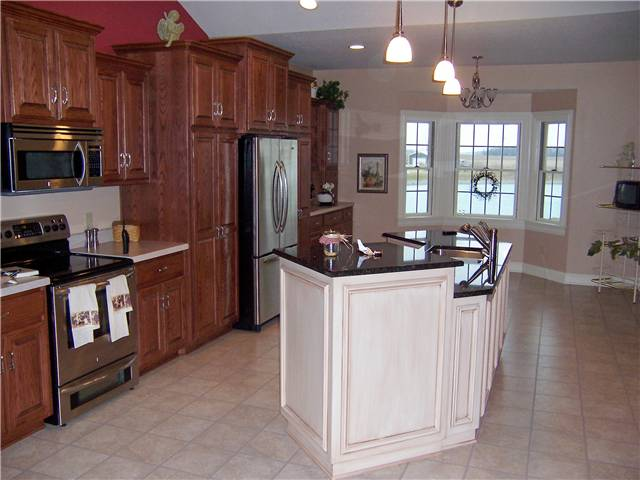 Red oak cabinets with a painted and glazed island - Raised panel doors - Standard overlay style - Dual level granite countertop on the islnnd