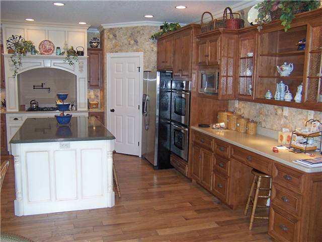 Hickory cabinets - Painted island and cooking area - Flat panel miter corner doors, drawer fronts, and side panels - Corian solid surface countertops