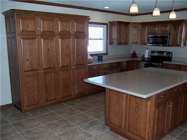 Red oak cabinets - Raised panel doors and side panels - Full overlay style - Full overlay style - Corian solid surface countertops