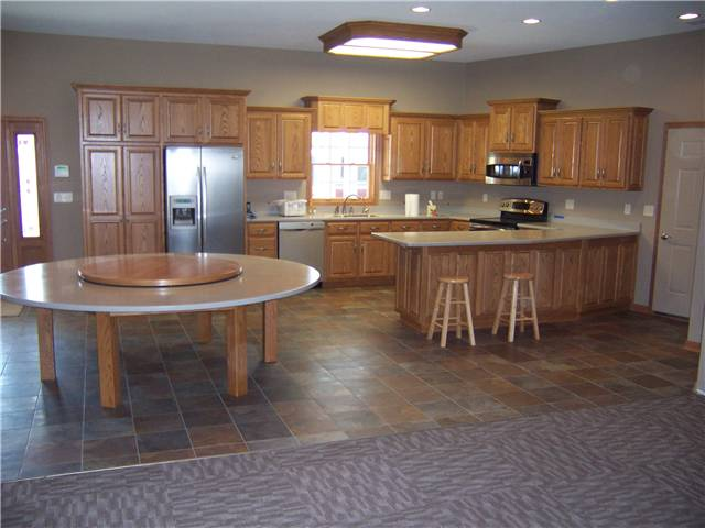 Red oak cabinets - Raised panel doors and side panels - Standard overlay style - Corian solid surface countertops and tabletop