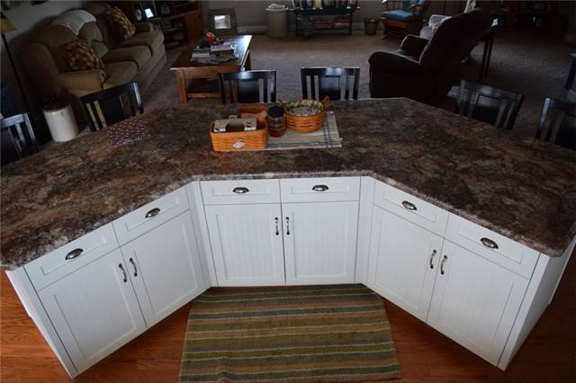 Painted large island with flat panel beadboard doors - full overlay style - laminate countertop