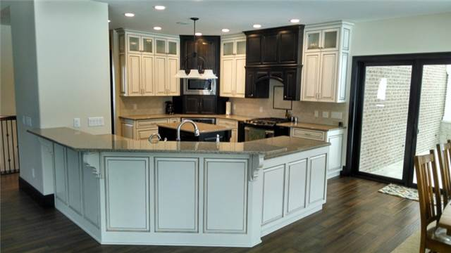 Glazed wood finish, dark stain for contrast, quartz countertops.