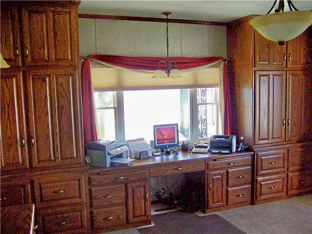 Oak computer desk with tall storage cabinets and file drawers. Office of an insurance agency.